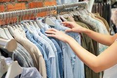 Руки выбирая одежды на шкафе в выставочном зале Стоковая Фотография