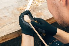 Руки высекая ложку от древесины, работая с концом зубила вверх Процесс делать деревянные ложку, зубило и shavings на грязной табл стоковые фотографии rf