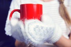 Руки в белых mittens и красных чае или coffe кружки стоковое изображение rf
