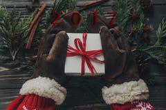 Руки в винтажных перчатках держа подарок на рождество с красным смычком o Стоковое фото RF