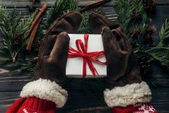 Руки в винтажных перчатках держа подарок на рождество с красным смычком o Стоковая Фотография RF