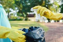 Руки в желтых перчатках выбирая вверх пустую пластмассы бутылки в сумку ящика Стоковая Фотография