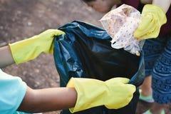 Руки в желтых перчатках выбирая вверх пустую пластмассы бутылки в сумку ящика Стоковое Изображение
