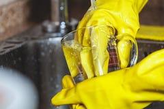 Руки в желтых резиновых перчатках моют чашки чая Стоковые Изображения RF