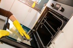 Руки в желтых защитных резиновых перчатках очищая печь Стоковое Фото