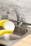 Руки в желтых перчатках моя белый шар под водой из крана Стоковое Фото