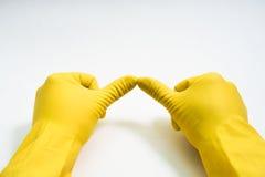 Руки в желтых резиновых перчатках на белой предпосылке Стоковые Изображения RF