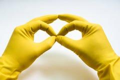 Руки в желтых резиновых перчатках на белой предпосылке Стоковая Фотография