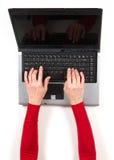 Руки в красной куртке и черной компьтер-книжке Стоковые Фото