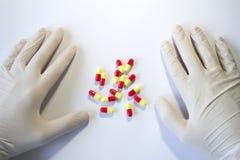 Руки в медицинских резиновых перчатках и красных и желтых капсулах Стоковое Изображение RF