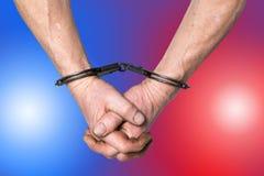 Руки в наручниках над полицией освещают предпосылку стоковые фото