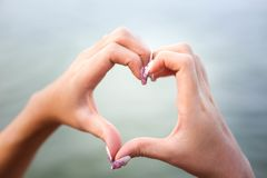 Руки в обрамлять формы сердца солнца на заходе солнца на пляже стоковые фото