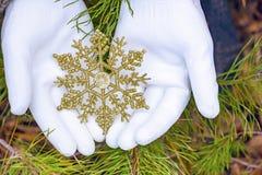 Руки в перчатках держат искусственную снежинку Стоковая Фотография