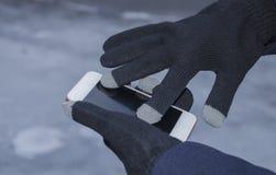 Руки в перчатках держат телефон Стоковая Фотография