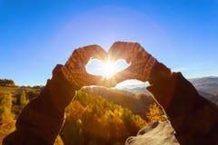Руки в перчатках делают сердце где лучи солнца светят Стоковая Фотография RF
