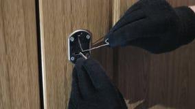Руки в перчатках раскрывая замок с picklocks акции видеоматериалы