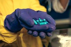 Руки в резиновых перчатках держа пилюльки в лаборатории, химической лаборатории Стоковое фото RF