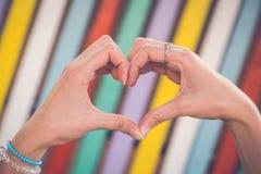 Руки в форме сердца против красочной предпосылки Стоковое Изображение RF