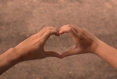 Руки в форме сердца влюбленности стоковые изображения rf