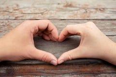 Руки в форме Харта на деревянной предпосылке Стоковая Фотография