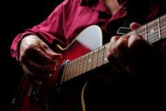 Руки гитариста и поднимающее вверх гитары близкое играть электрической гитары Сыграйте гитару Стоковые Фото