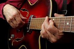 Руки гитариста и поднимающее вверх гитары близкое играть электрической гитары Сыграйте гитару Стоковая Фотография