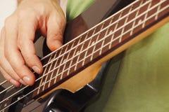 Руки гитариста утеса играя электрическую басовую гитару Стоковые Фото