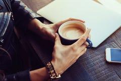 Руки девушки держа чашку кофе на предпосылке a Стоковое Фото