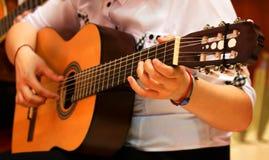 Руки девушки играя гитару Стоковое Изображение