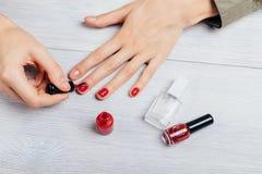 Руки девушки прикладывают красный блеск на ногтях рядом с бутылками стоковое фото