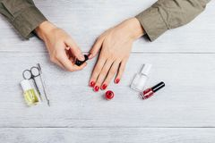 Руки девушки прикладывают красный блеск на ногтях рядом с ножницами стоковые изображения