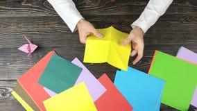 Руки делая цветок origami с желтой бумагой сток-видео