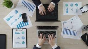 Руки деловых партнеров печатая на компьтер-книжках напротив одина другого, переговорах акции видеоматериалы
