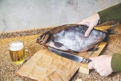 Руки держат больших отрывистых рыб и большого ножа Стоковые Фото