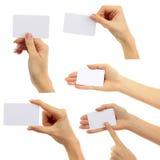 Руки держат коллаж визитных карточек на белой предпосылке Стоковое фото RF