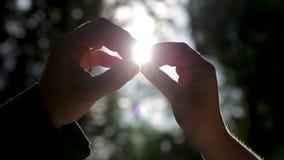 Руки держат кольца близкий против лучей солнца Оценивающ ювелирные изделия или получающ женатый акции видеоматериалы