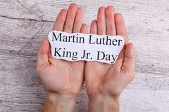 Руки держат на ладонях бумажного знака с младшим Мартин Лютер Кинга надписи день стоковые изображения