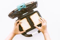 Руки держат тостер при куски хлеба делая механический инструмент быстрый Стоковые Изображения
