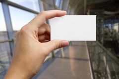 Руки держа белую карточку id делового визита, подарок, билет, пропуск, присутствующий конец показа вверх на запачканной голубой п стоковая фотография