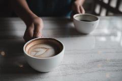 Руки держа 2 белых чашки горячего кофе на таблице в кафе Стоковые Изображения