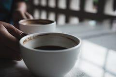 Руки держа 2 белых чашки горячего кофе на таблице в кафе Стоковое фото RF