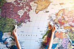 Руки держа деревянных маленьких людей на предпосылке карты Стоковое Изображение