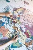 Руки держа деревянных маленьких людей на предпосылке карты Стоковые Фото