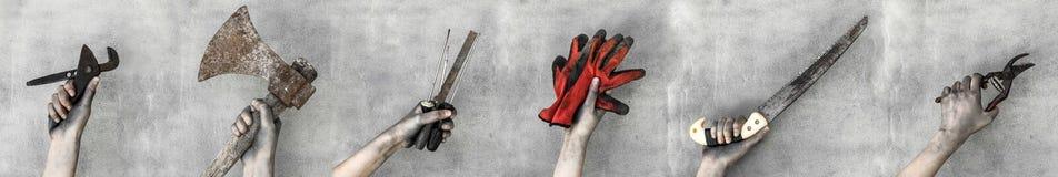 Руки держа инструменты деятельности изолированный на серой предпосылке стоковое изображение rf