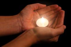 Руки держа и защищая освещенный или сгоренный свет горящей свечи свечи на темноте Стоковая Фотография RF