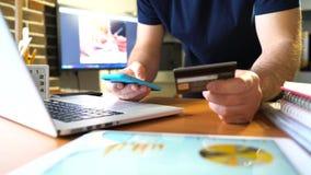 Руки держа кредитную карточку и используя smartphone сток-видео