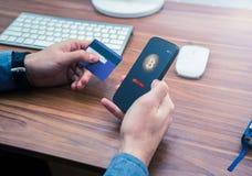 Руки держа кредитную карточку и телефон приобретение bitcoin онлайн стоковая фотография