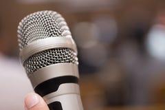 Руки держа микрофоны для говорить в конференц-зале стоковые изображения rf