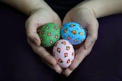 Руки держа 3 пасхального яйца Стоковое Фото