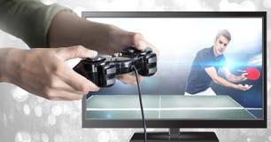Руки держа регулятор игры с настольным теннисом на телевидении стоковые фото